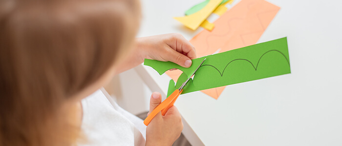 A Child Developing Fine Motor Skills by Cutting Paper