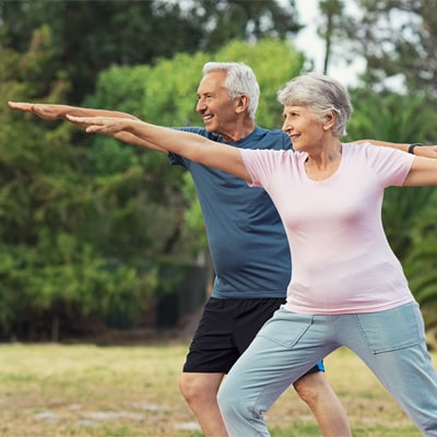 Old couple doing yoga in the sun